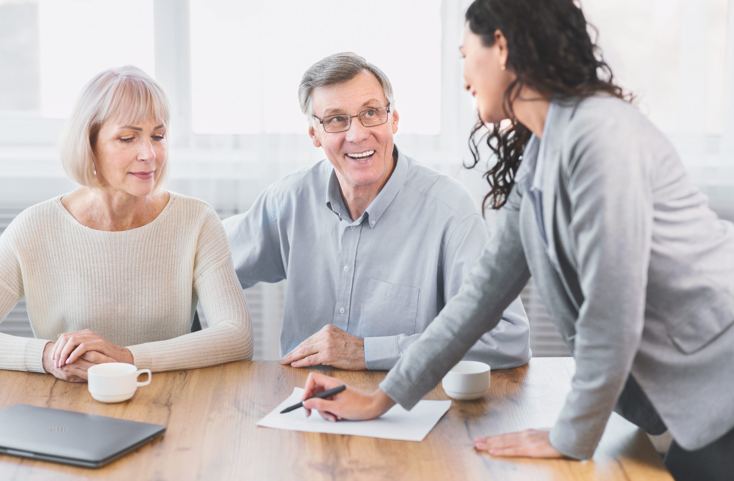 happy mature couple talking to financial advisor a 8WW8X5M