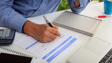 man preparing an insurance claim form PH7SDNH