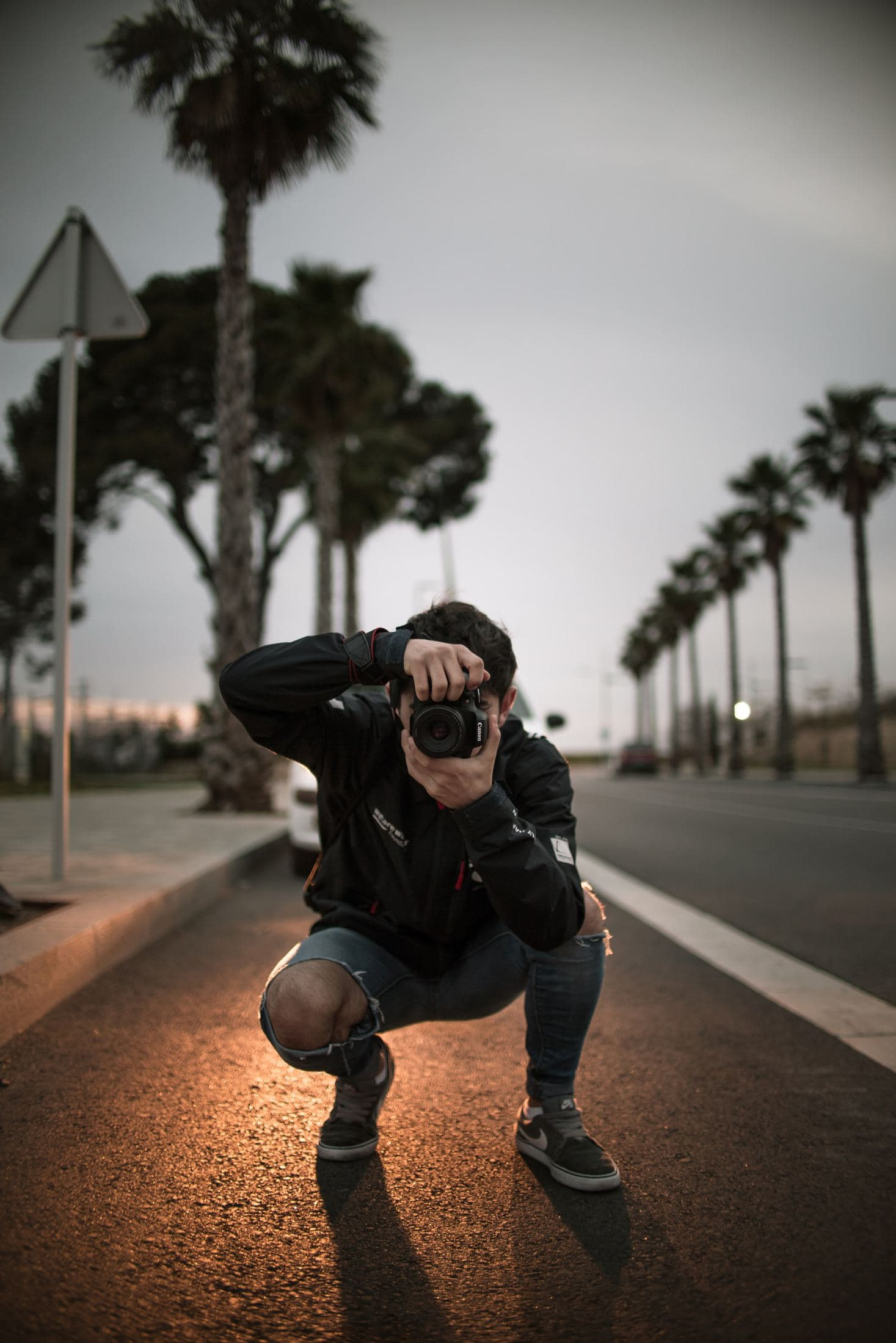 man wearing blue ripped jeans holding DSLR camera
