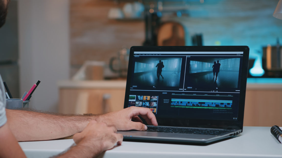 videographer working remotely editing video footag 748CU2Z