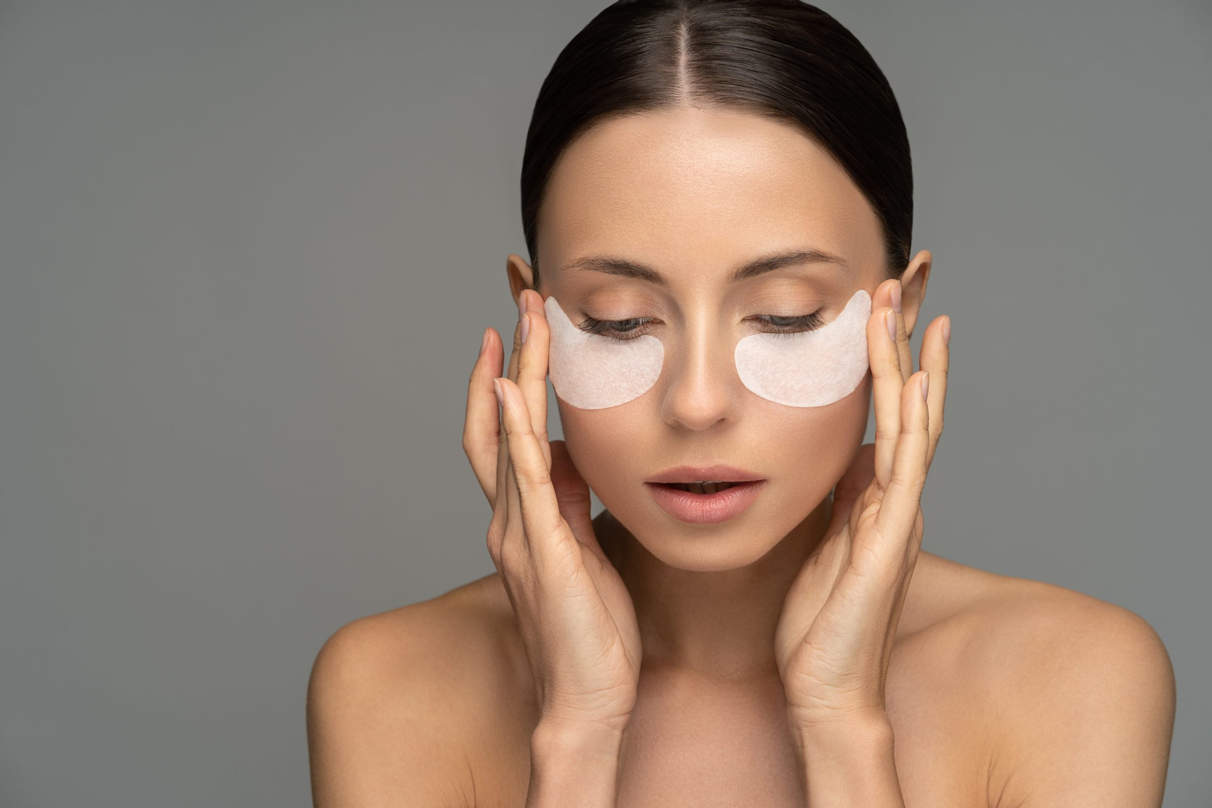 woman applying hydrogel under eye recovery patches FS5JHAT
