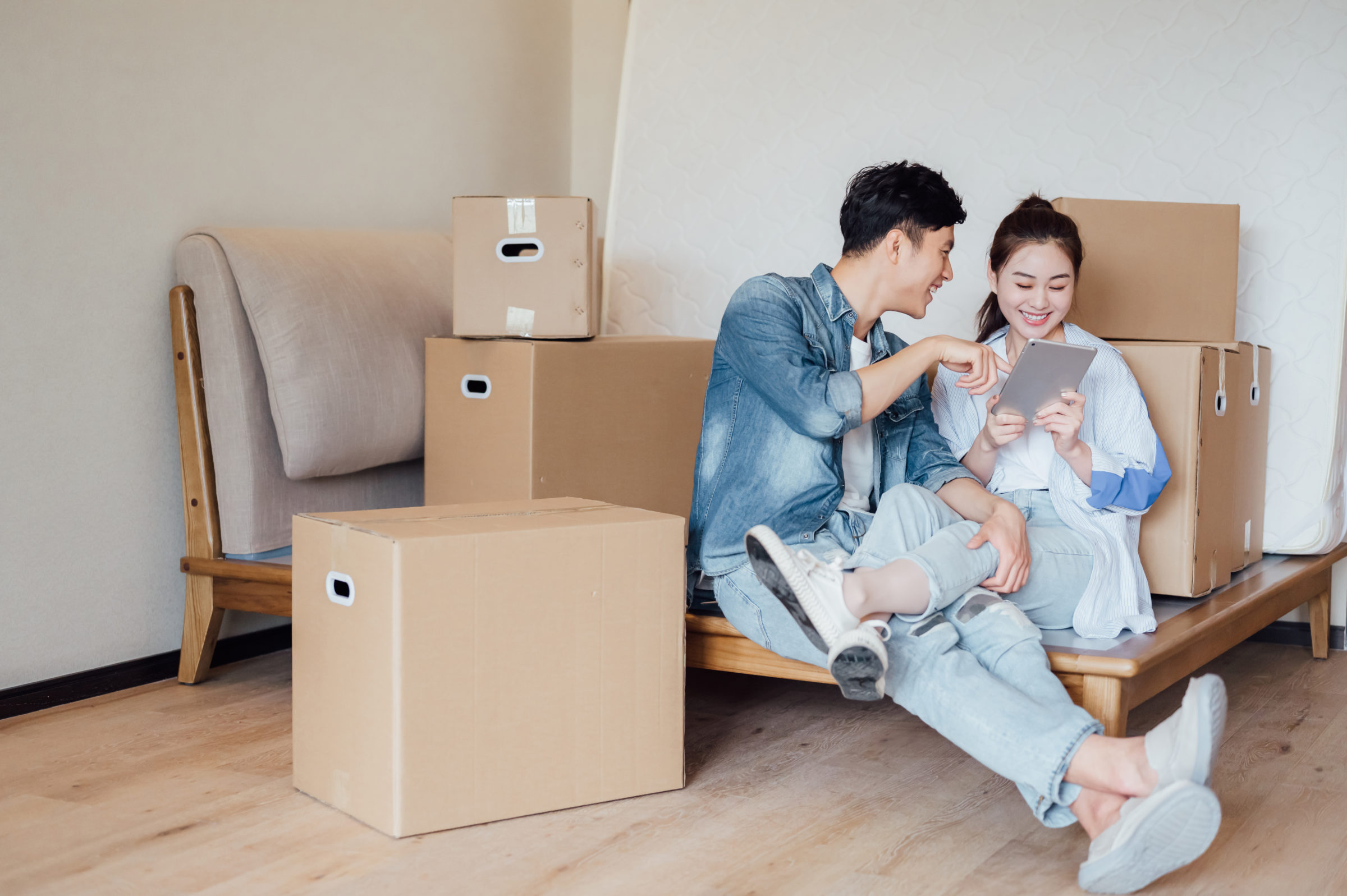 young couple using ipad during moving house QPVGDS3