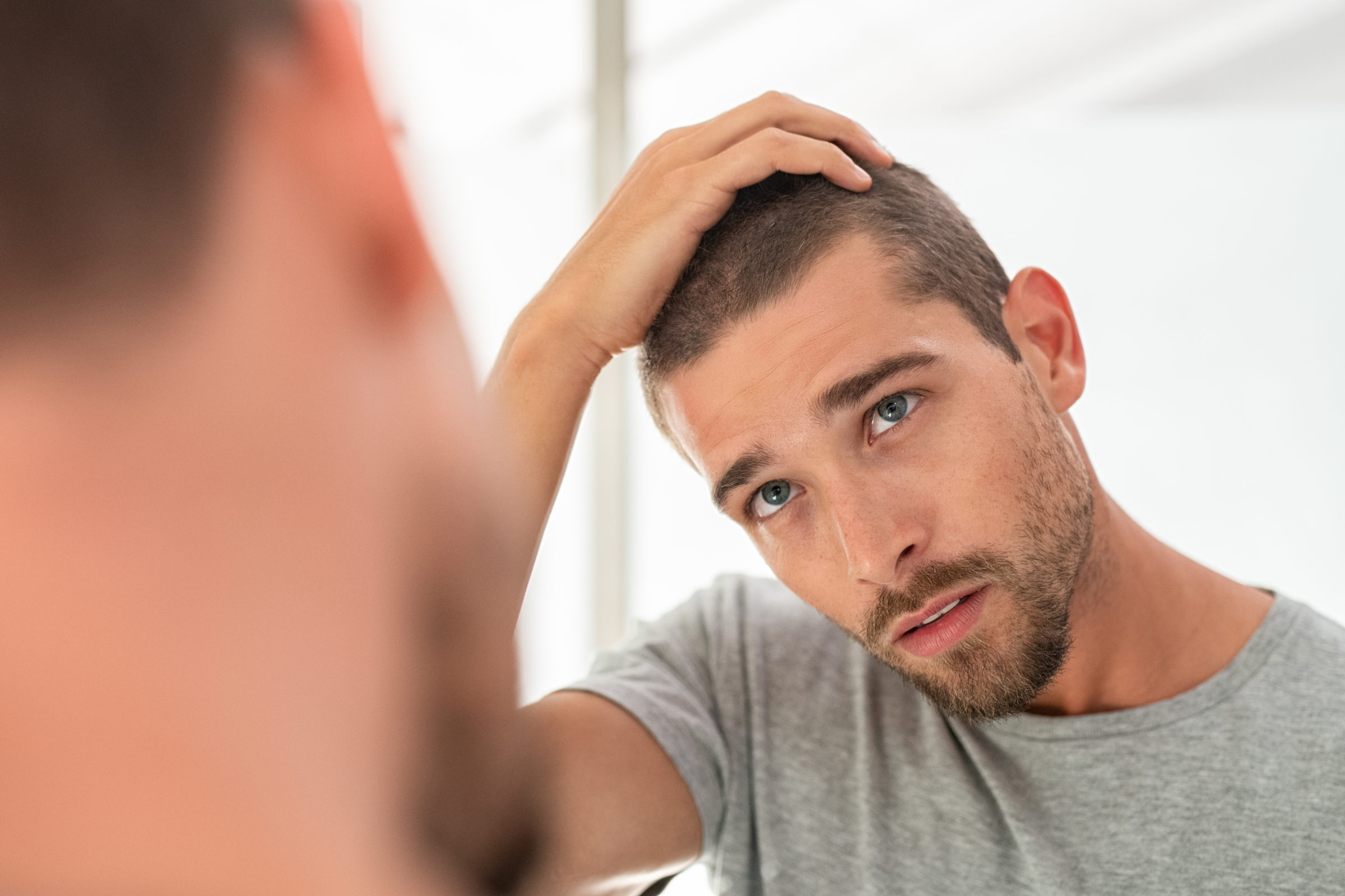 young man checking hair in mirror J82DGS9