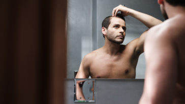 young man in bathroom worried about premature rece USD2ZPG