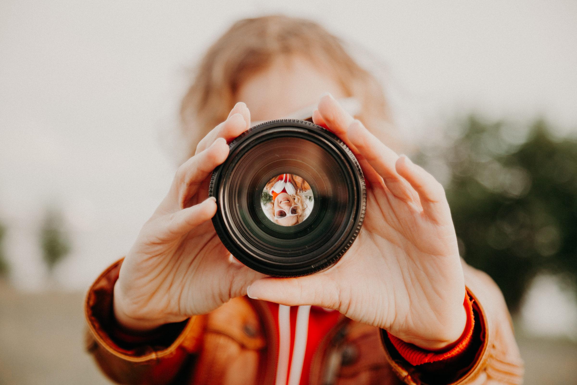 young woman looking through camera lens photograph SEKDFMB