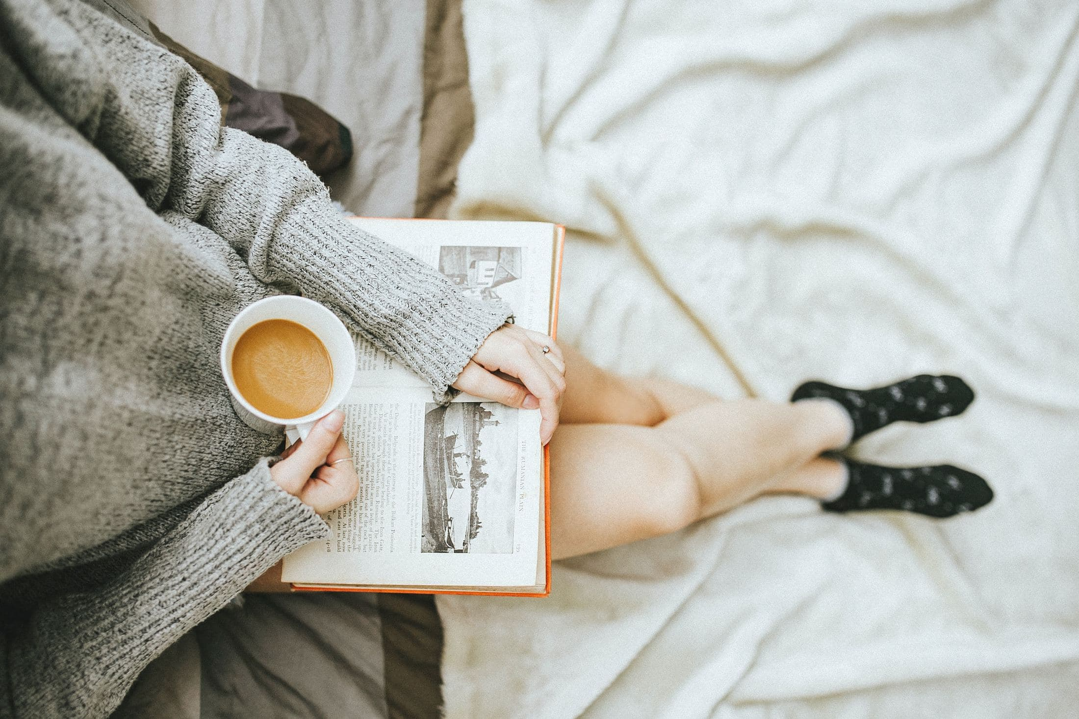 woman holding a cup of coffee at right hand and reading book on her lap while holding it open with her left hand in a well-lit room
