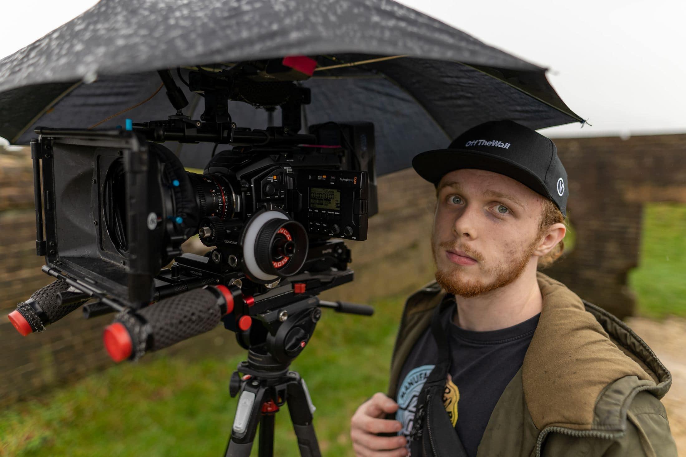 man in brown jacket holding black camera