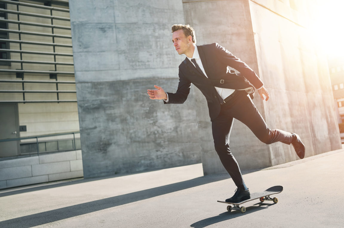 extremal man wearing suits rides a skateboard PGP664V