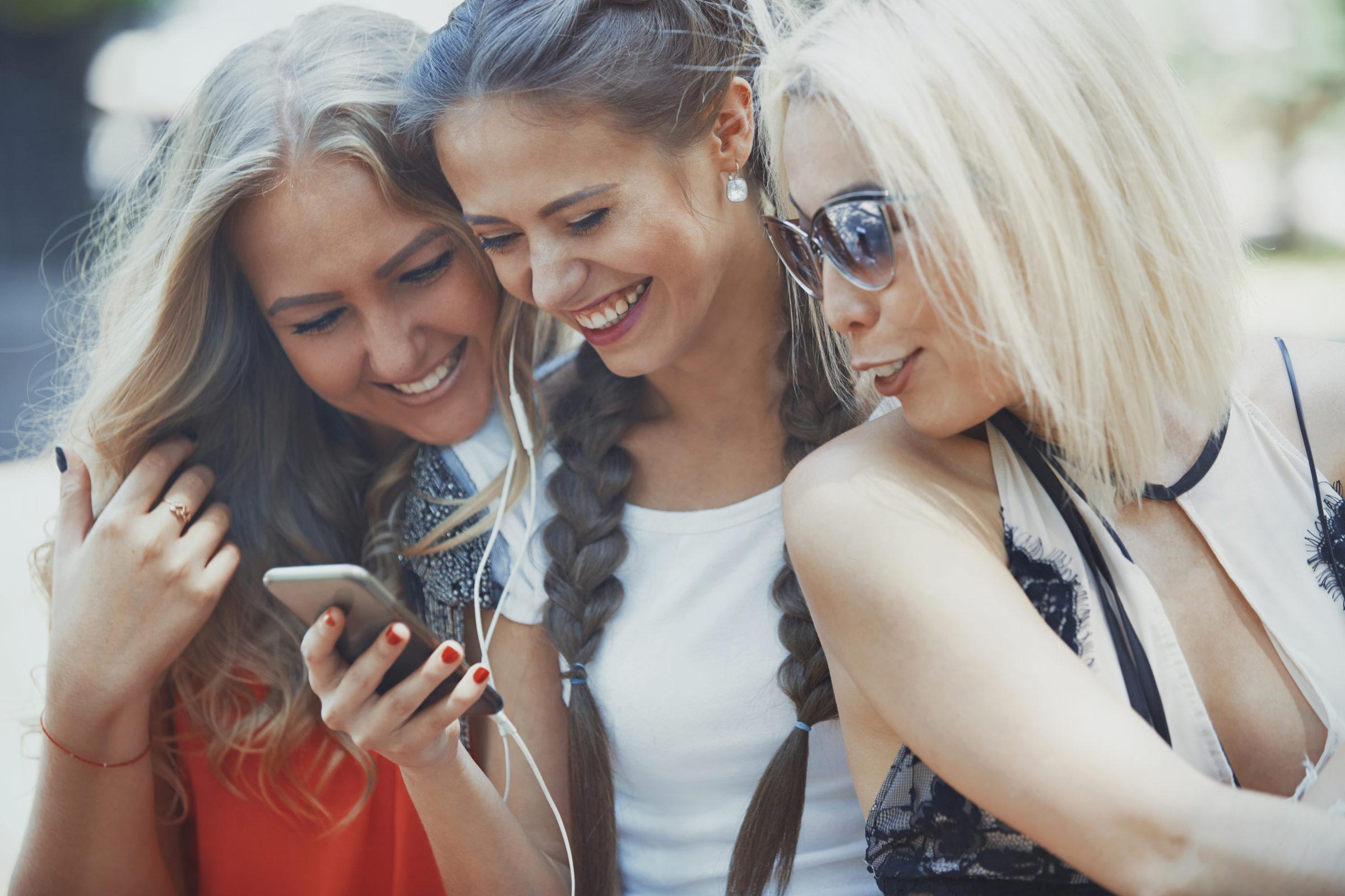 girlfriends using smartphone and having fun in soc RJVE7ME