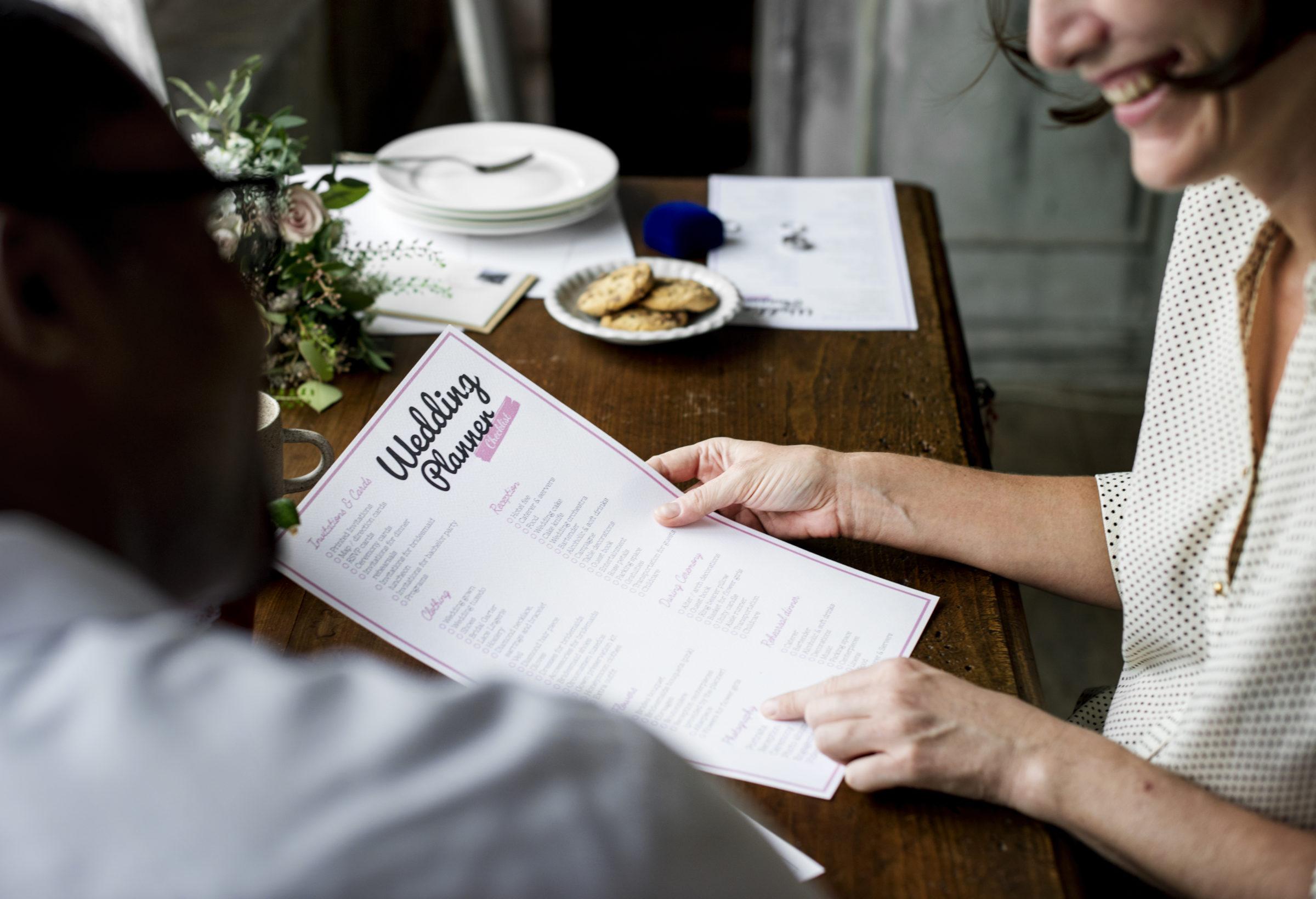 hands holding wedding planner checklist informatio PSGQEUR