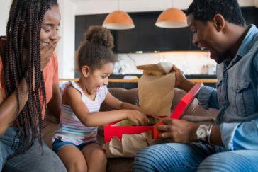 little girl receiving gift from her parents 2021 04 22 23 31 03 utc