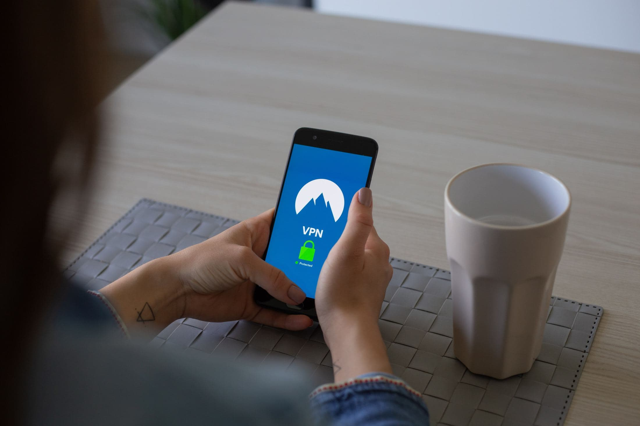 person holding black smartphone besides white cup