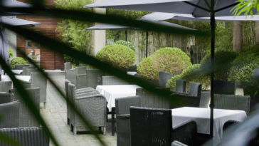 seating on a paved patio with sun umbrellas 83Y9M6Y