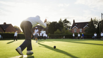 a lawn bowls player standing on a small yellow mat QKYQT7B