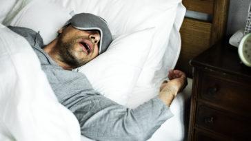 a man sleeping on a bed 54F2XGK