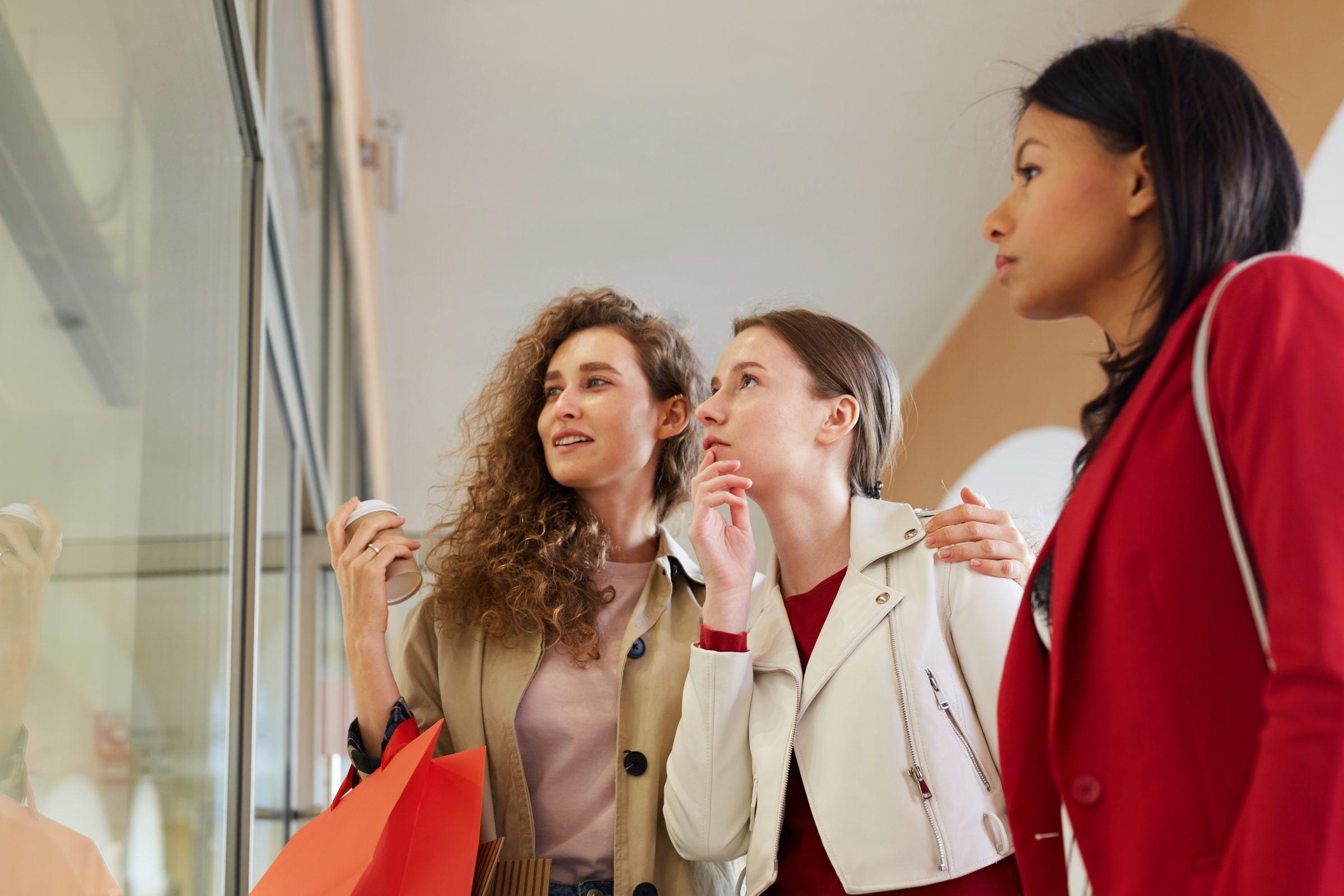 girls choosing dress in shopping display QDXG6NP