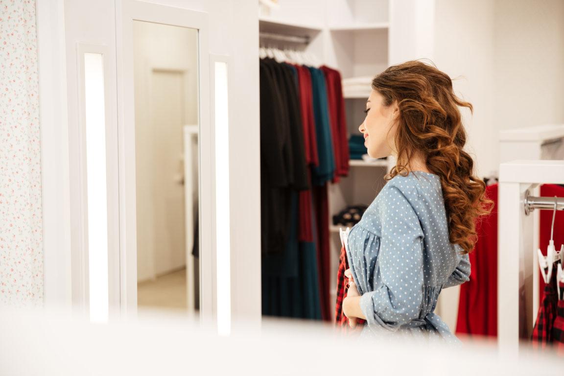 smiling woman shopper in blue dress choosing cloth PTZQRHN