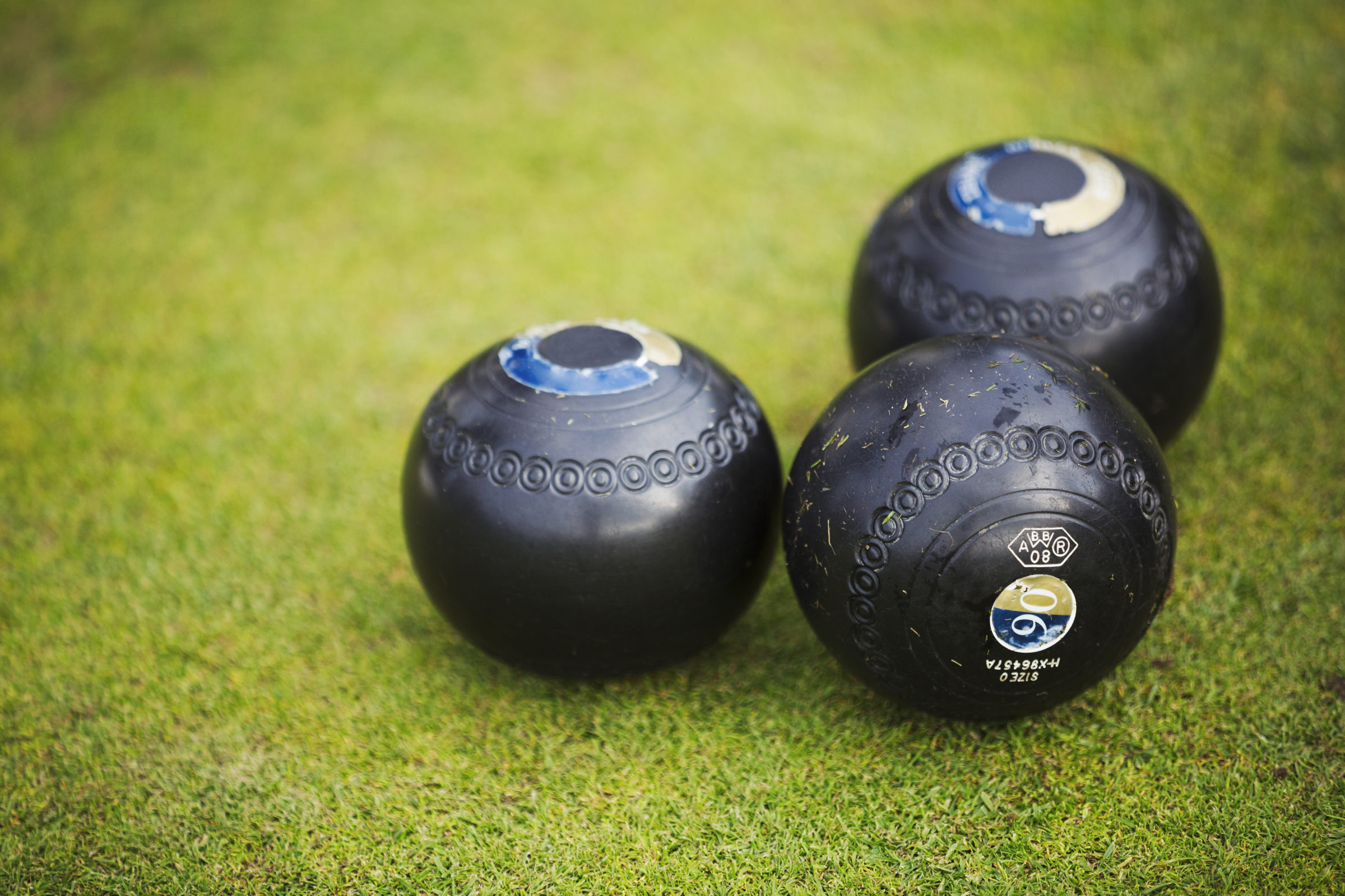 three round wooden black lawn bowls on a smooth pl MA4DXS9
