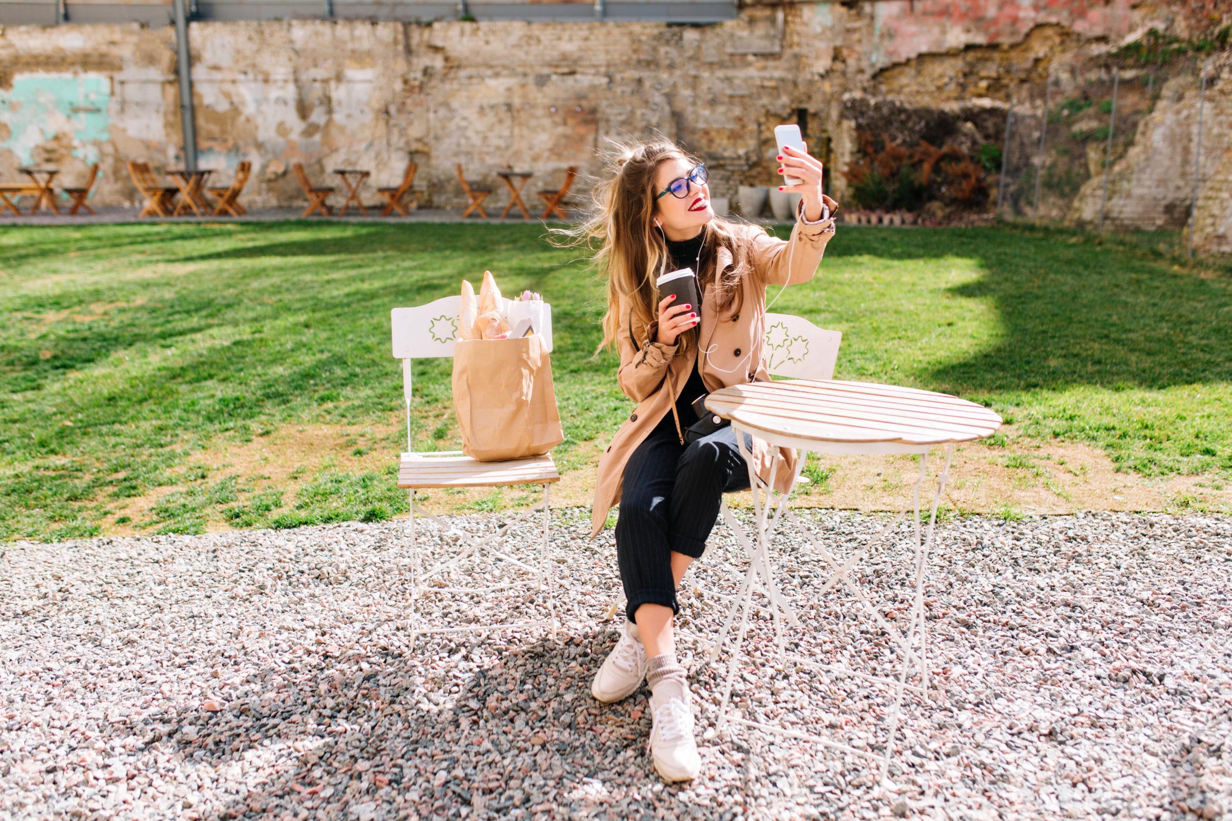 attractive hipster girl wearing beige coat makes s Z7SJ2EE