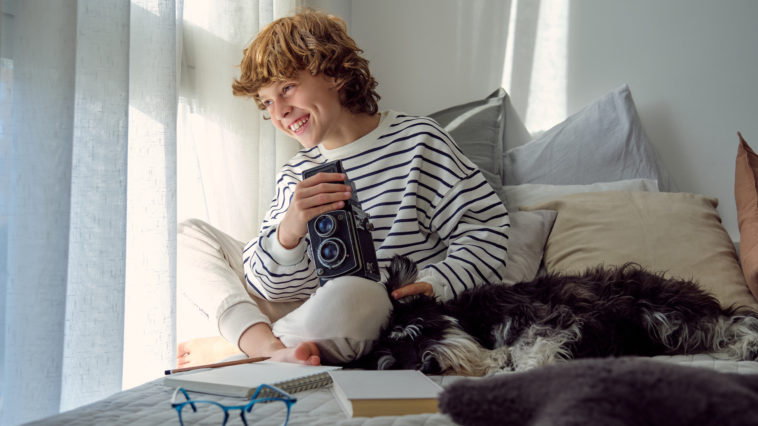 cheerful boy with vintage photo camera and dog on KQBQXTS