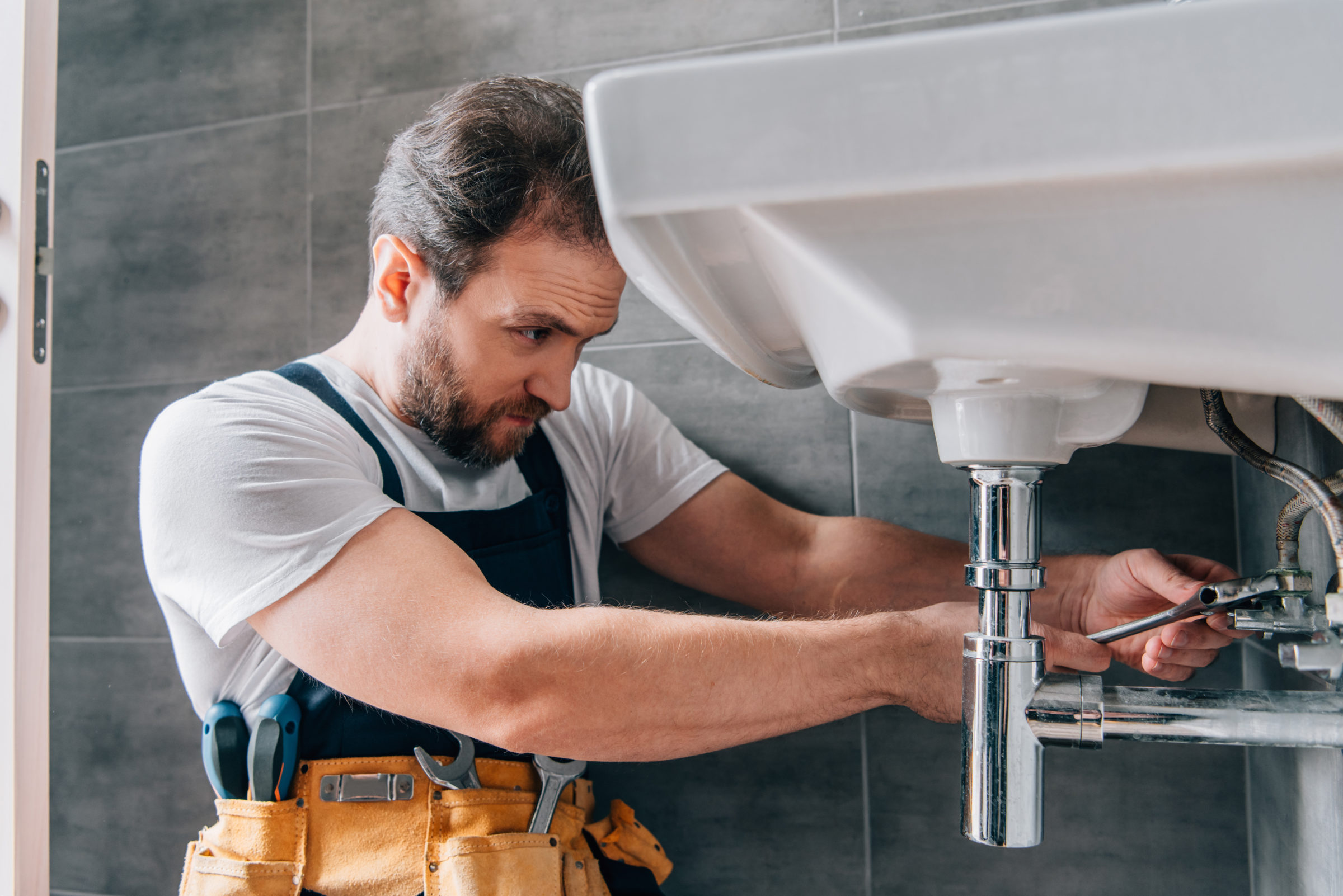 focused male plumber in working overall fixing sin HGY4LYV