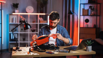focused man repairing remote controlled toy car 9B58U4A