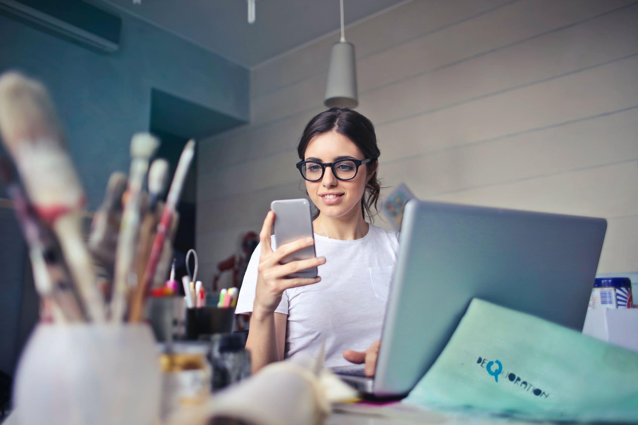 woman in white shirt using smartphone