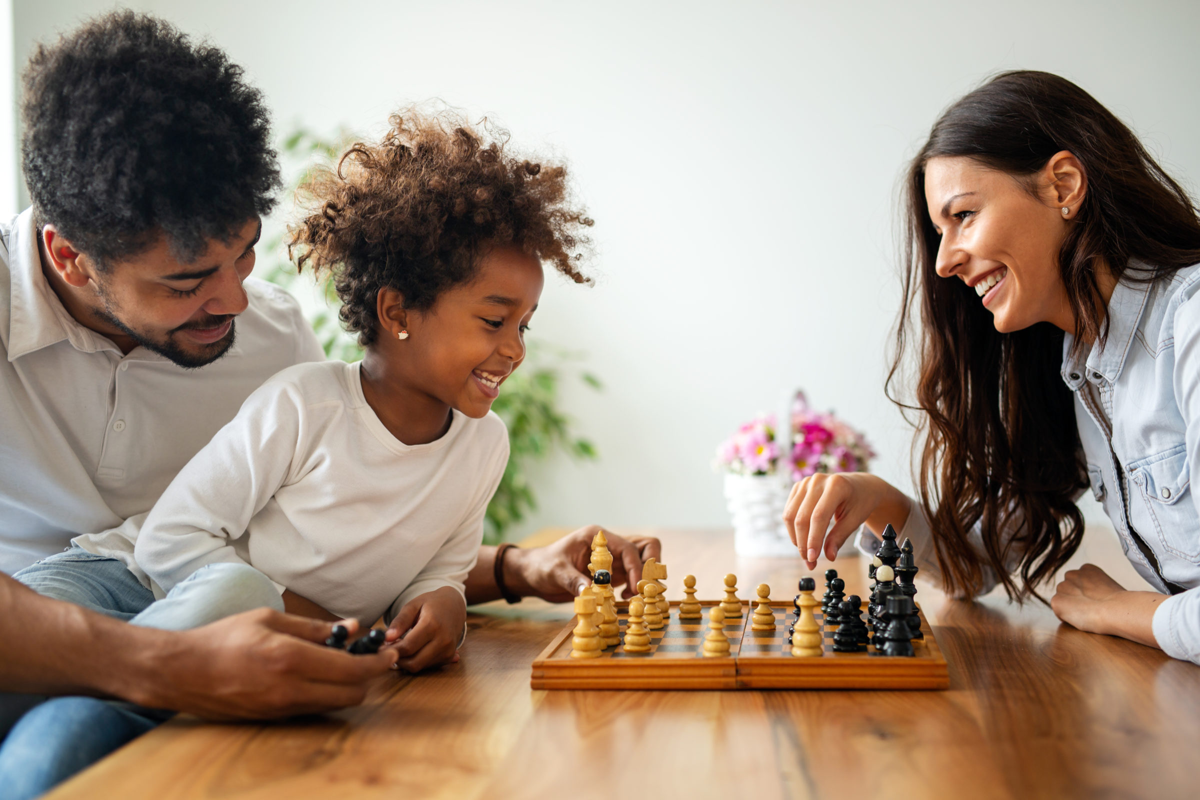 parents and child playing chess while spending tim NUHLK3H
