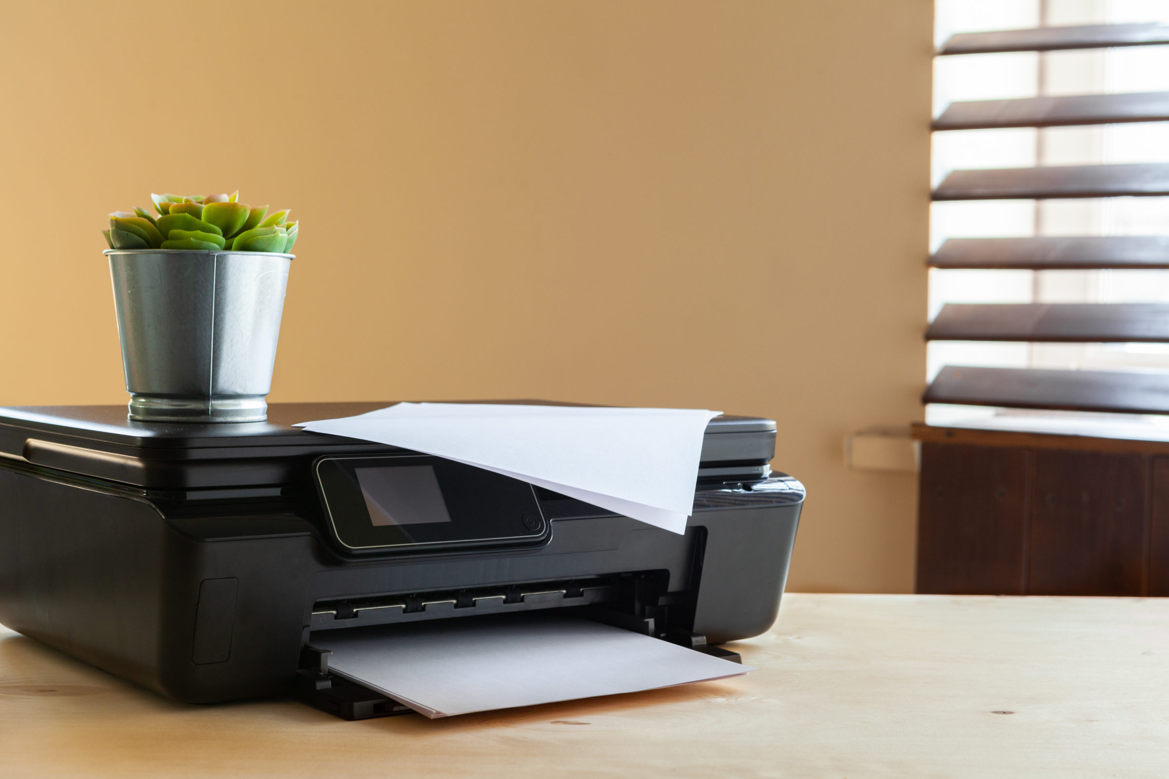 front view of a black printer machine on a table 4EA3YUE