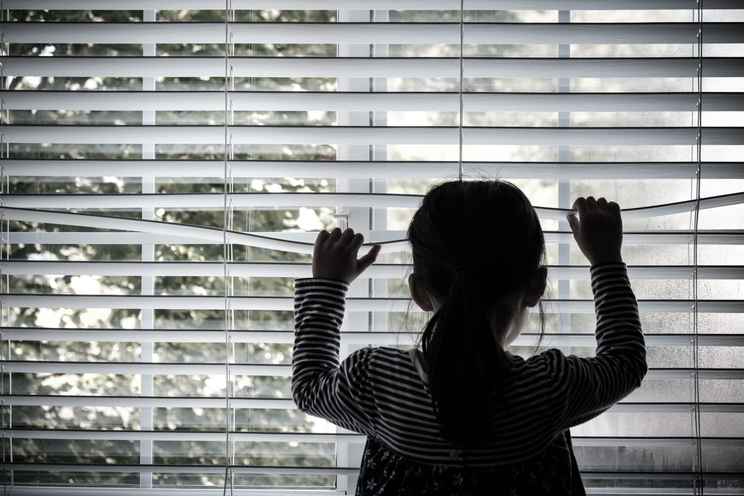 lonely little kid in front of a window 5NT8QZE