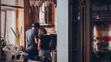 man and woman standing in front of gas range