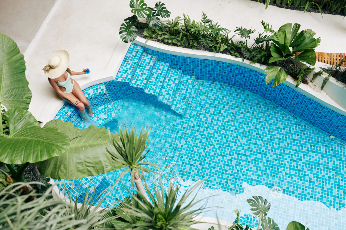woman resting by swimming pool SBNFBBR